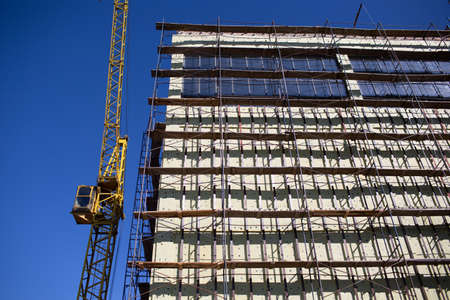 Building with construction crane and scaffolding blue sky.