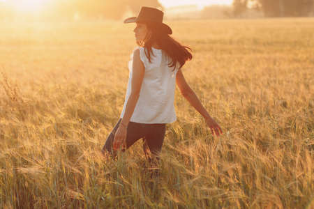 Woman farmer in cowboy hat walking with hands on ears at agricultural field on sunset