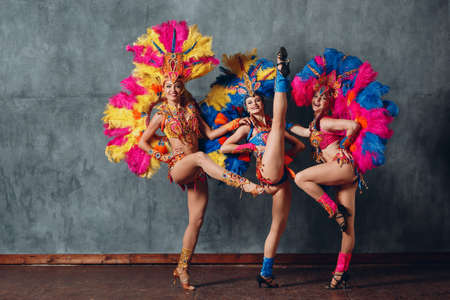 Three Woman in cabaret costume with colorful feathers plumage Standard-Bild