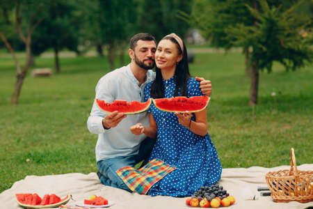 Young adult woman and man couple picnic at green grass meadow in park having fun with watermelon