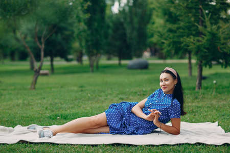 Beautiful young adult woman in blue dress picnic at meadow in park Stok Fotoğraf - 154528964