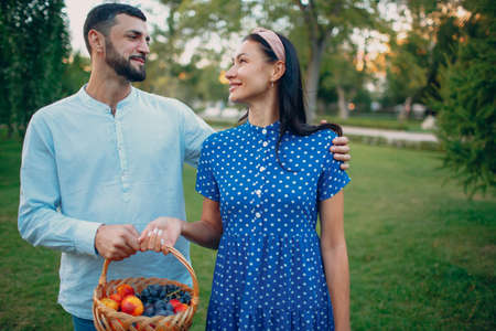 Happy Couple with Fruits in Picnic Basket Staying in the Park. Stok Fotoğraf - 154528985