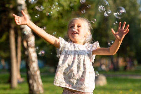 Little cute girl in the summer park blowing bubbles and having fun