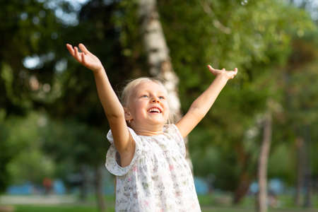 Cute Siling Little Blond Girl with Raised Open Arms in The Park Having Fun.
