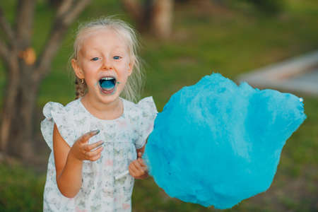 Little blond girl eating cotton candy and shows blue tongue in the park.
