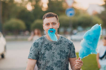 Young adult man with beard made of blue cotton candy. Stok Fotoğraf