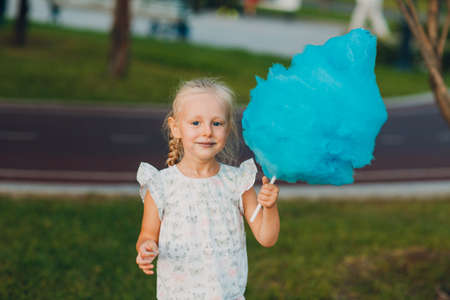 Little blond girl eating blue cotton candy in the park. Stok Fotoğraf - 154845773
