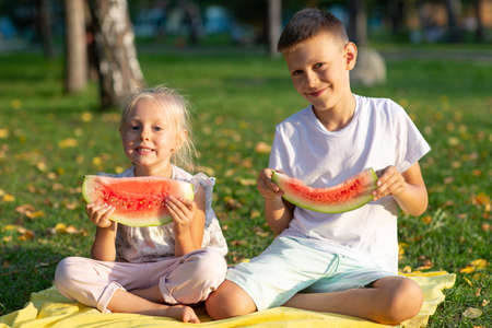 To cute kids lttle boy and girl eating juicy watermelon in the autumn park meadow Stok Fotoğraf - 154783401