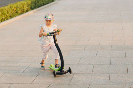 Little girl using a scooter on the city street. Stok Fotoğraf