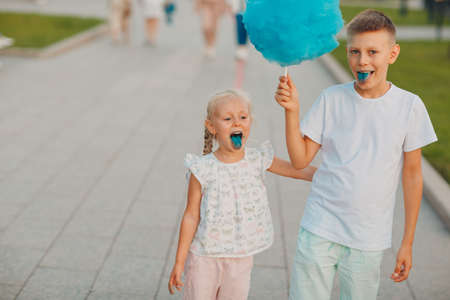 Happy children boy and girl eating blue cotton candy outdoors Stok Fotoğraf - 154783407