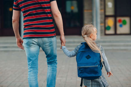 Rear view of father walking back to school with his daughter carrying backpack Stok Fotoğraf - 154753834