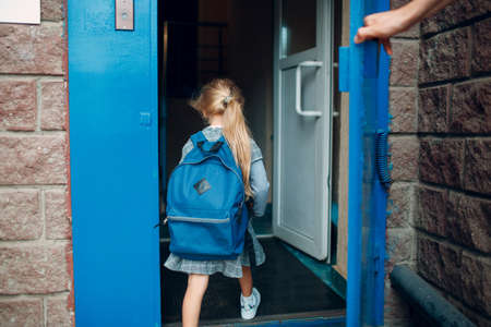 Rear view of father come back to home from school with his daughter carrying backpack