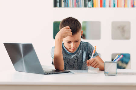 Young boy in headset sitting at table with laptop and preparing to school. Online education concept.