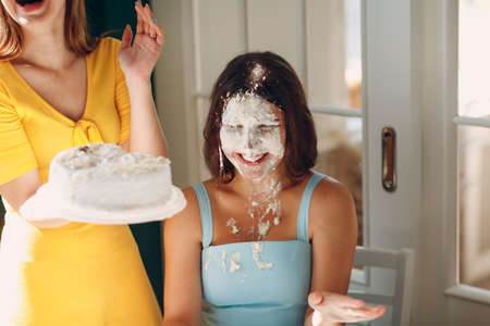 Young woman dip face in white cake with cream. Happy birthday concept. Stok Fotoğraf - 154782514