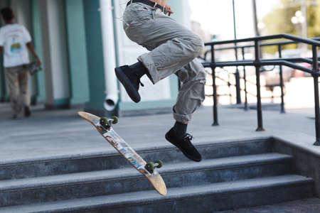 Young boy riding trick on skateboard in city Stok Fotoğraf - 154782521
