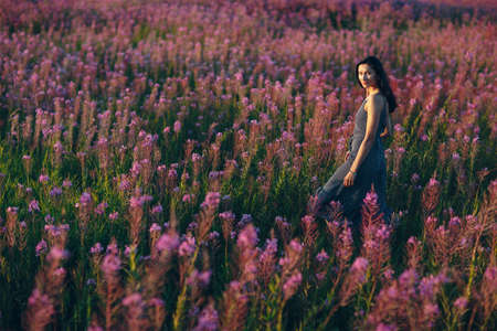 Girl on blooming flower field. Lilac flowers and woman.