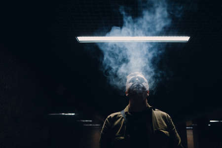 Portrait of young caucasian man smoking e-cigarette in dark with line light