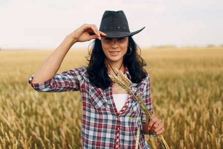 Woman american farmer wearing cowboy hat, plaid shirt and jeans at wheat field