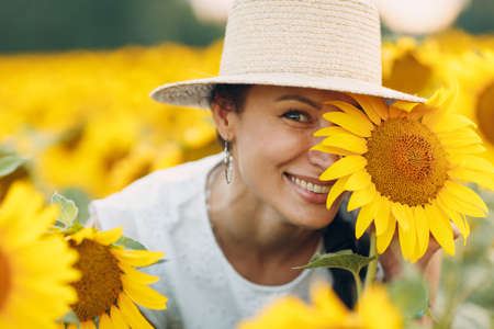 Beautiful smiling young woman in a hat with flower on her eye and face on a field of sunflowers Stok Fotoğraf