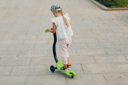 Little girl riding a scooter on the city street.