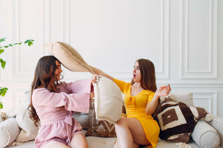 Women happy friends at home sitting and fight with pillows and smiling with white birthday cake