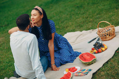 Young adult woman and man couple picnic at green grass meadow in park with fruits and basket. Stok Fotoğraf - 154764226