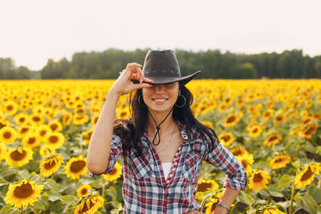 Young woman agronomist wearing cowboy hat, plaid shirt and jeans on sunflower field. Rich harvest concept.
