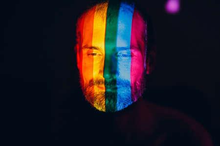 Rainbow Flag on face of adult man in dark. Stok Fotoğraf - 154753743