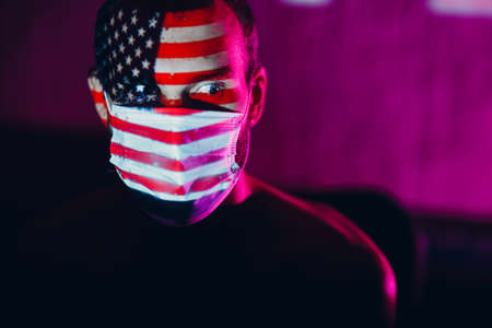 Adult man in medical face mask with USA flag on his face in the dark. Stok Fotoğraf