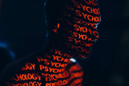 Young adult man with word Psychology on his face in the dark. Stok Fotoğraf - 154753779