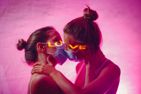 Portrait of two kissing couple young women in medical face mask