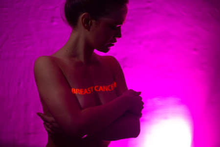Young adult woman with words Breast Cancer on her chest Stok Fotoğraf