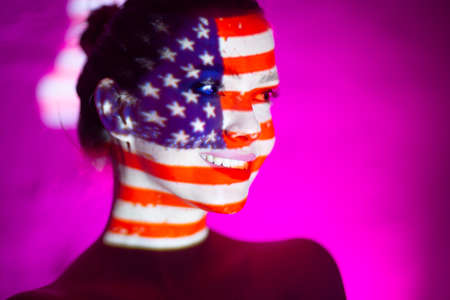 Young woman smiling with USA flag on her face