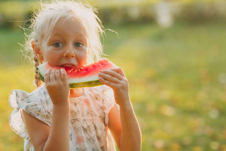 Cute blond little girl eat watermelon on the grass in park