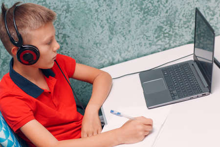 Young student boy with laptop writes pen learning and preparing back to school Stok Fotoğraf