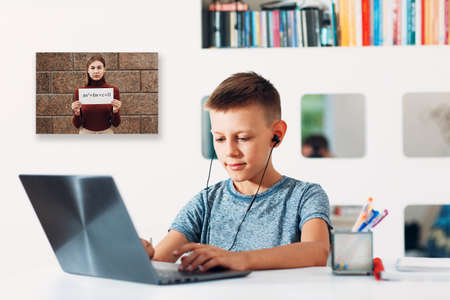 Young boy in headset sitting at table with laptop and preparing to school by teacher with white poster and quadratic equation on computer screen. Online education concept.