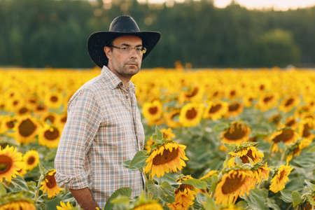 Man farmer standing in a sunflower field.