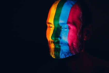 Rainbow Flag on face of adult man in dark.