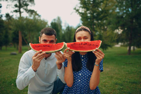 Young adult woman and man couple picnic at green grass meadow in park having fun and smile with watermelon Stok Fotoğraf