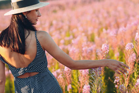 Girl in hat on blooming Sally flower field. Lilac flowers and woman.