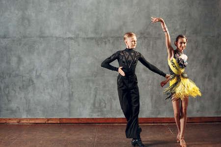 Young couple sport dancers dancing in ballroom dance cha-cha-cha. Stok Fotoğraf