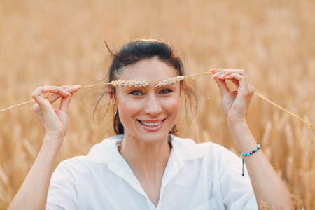 Portrait of a beautiful smiling brunette woman with ears of wheat on her eyebrows