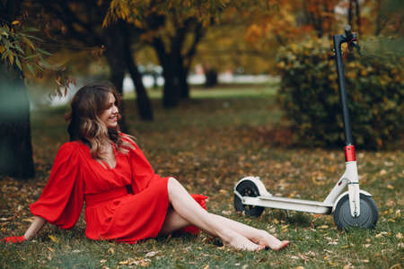Young woman sitting with electric scooter in red dress at the autumn city park