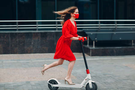 Young woman with electric scooter in red dress and gloves with face mask at the city. New normal fashion and coronavirus COVID protection concept.