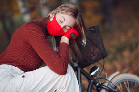 Young woman riding bicycle in red gloves and face mask at autumn park Stok Fotoğraf