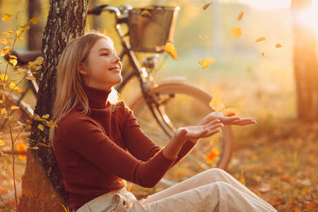 Happy active young woman sitting with vintage bicycle in autumn park at sunset