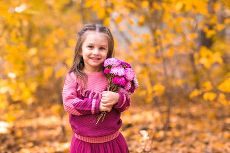 Cute little girl in autumn park with pink flower bouquet