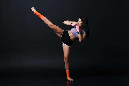 Sportsman muay thai woman boxer posing in training studio at black background. Foto de archivo