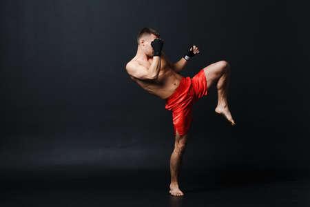 Sportsman muay thai man boxer stance ad knee kick at black background