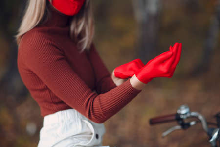 Young woman riding bicycle and put on red gloves and face mask at autumn park